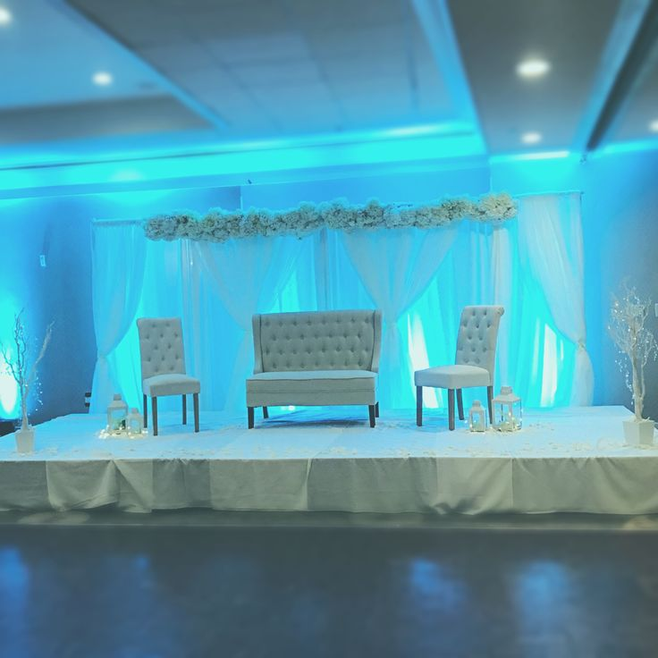 Blue uplighting with white furniture rentals makes a beautiful wedding photo backdrop in Independence Ballroom at Valley Forge Casino Resort #Idovfcr