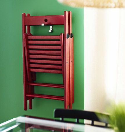 A folding IKEA chair in red wood, hung up on a hook on the wall.