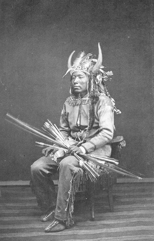 Comanche Indian This is a cabinet card photo of an unidentified Comanche Indian wearing his war regalia. Date: Between 1870 and 1879