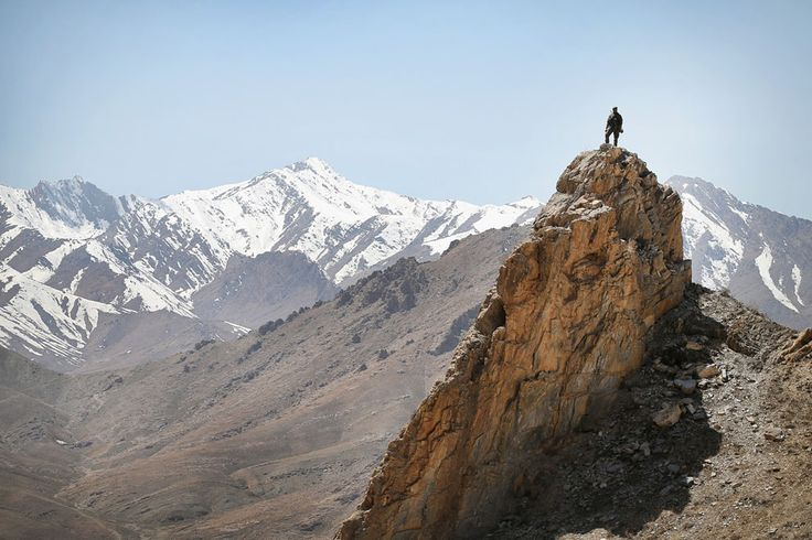 An Afghan National Army soldier looks out from a rocky overlook as soldiers with the U.S. Army's 2nd Battalion 87th Infantry Regiment, 3rd Brigade Combat Team, 10th Mountain Division patrol below on March 31, 2014 near Pul-e Alam, Afghanistan. (Scott Olson/Getty Images)   www.theyearthatwas.in #TheYearThatWas