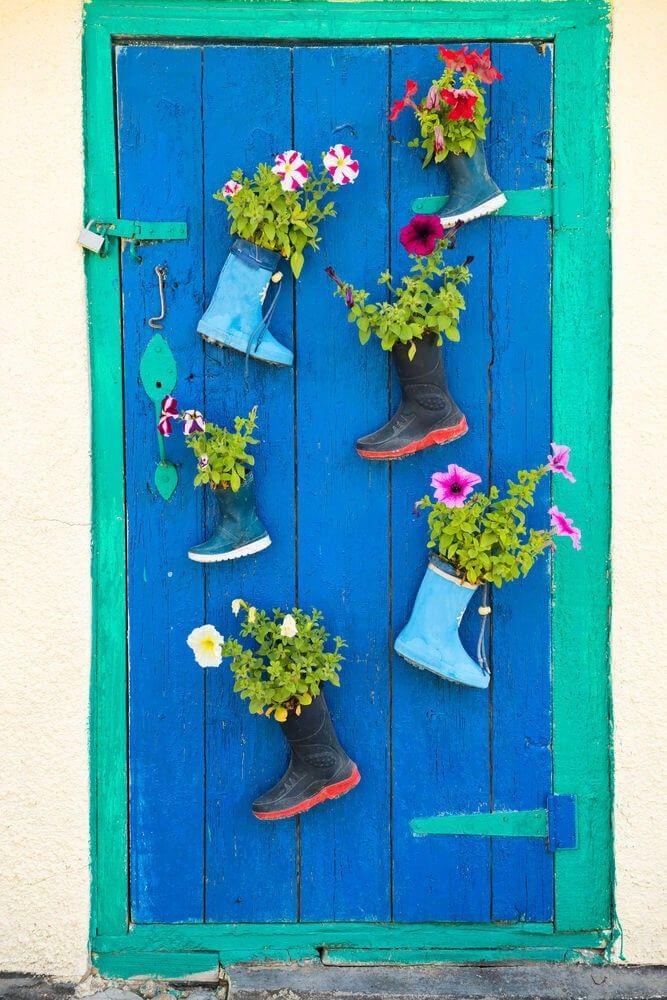 Eine bunt bemalte hölzerne Tür ist mit drei Paar Gummistiefel verziert, die sich harmonisch mit der Tür-Farben entsprechen. Diese Gummistiefel dienen als Tür montiert Pflanzgefäße mit bunten Blumen, die einen reichen spielerischen Kontrast zu der Tür Ozean Farbtöne bieten.