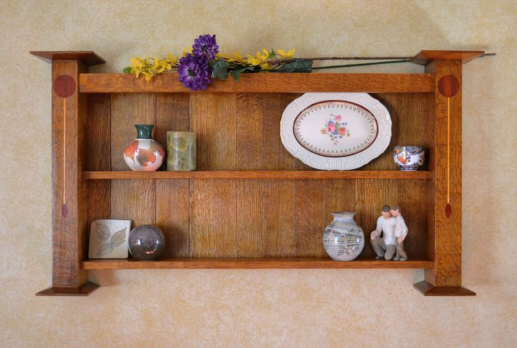 This marvelous Arts and Crafts (or Craftsman) Wall Shelf features two large columns with a a flower/stem/leaf inlay. Two shelves will handsomely display your best decorative items or photographs. You won't find another piece like this.Post view2  Made of all quarter-sawn white oak (with the exception of the inlay), and traditional bullet-proof mortise and tenon joinery, this piece will not only look great for decades, but be solid today as when your heirs fight over it.  43″ wide, 23″ tall…