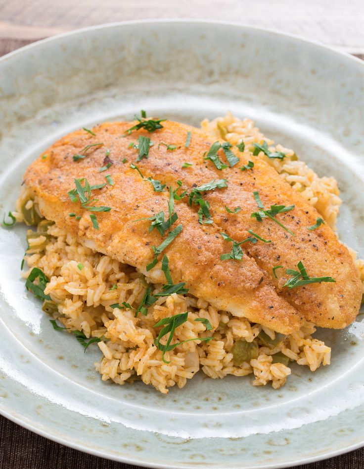 """This dish, inspired by generations of backyard fish fries in the heart of Cajun Louisiana, is rustic Southern fare at its best. We're pan-frying catfish, a Southern staple, and serving it over """"dirty rice,"""" or brown rice simmered with traditional Cajun spices, onion, celery and green bell pepper."""