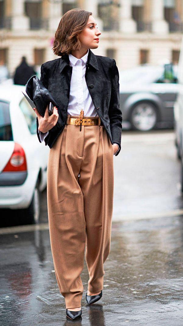 Mulher posa para foto de street style usando camisa branca, blazer preto, calça pantalona camelo, scarpin preto, clutch preta e cinto dourado
