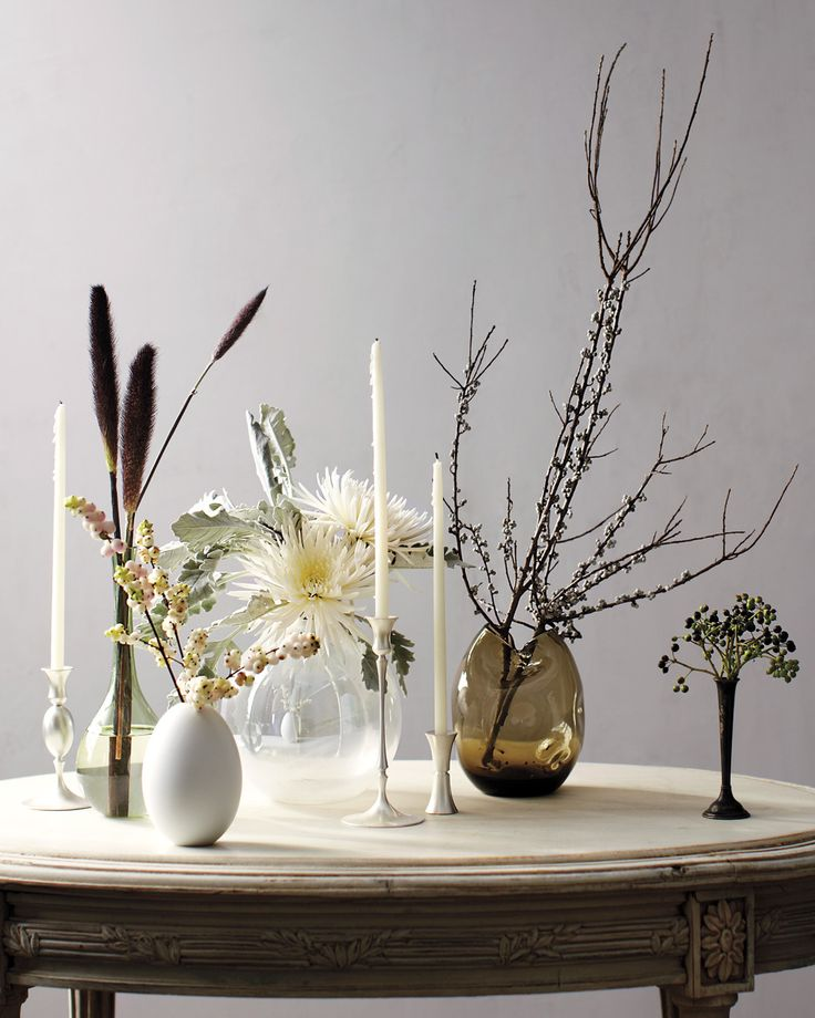 In late fall, nature's shapes become stark and geometric. Highlight plants that may be overlooked outdoors by placing a few stems of one or two types in their own eclectic vases. From left: Black-leaf millet grass, snowberry, dusty miller with spider mums, bayberry, and ivy berries. Candlesticks, in Satin Silver Finish, from $156 each, and Egg vase, in White With Bisque Exterior and Glazed Interior, $259; by Ted Muehling; erbutler.com.