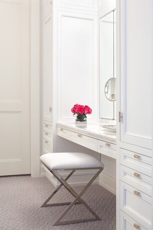 Fabulous walk-in closet features stacked cabinets flanking unset mirror over built-in vanity topped with marble and paired with polished chrome X stool.