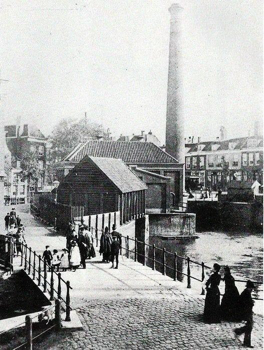 """Slaakvaart, het stoomgemaal.  Hier heeft eerst de in 1742 gebouwde stenen watermolen bij de Oostpoort gestaan. In de volksmond heette deze molen """"Kostverloren"""" . Foto is van vóór 1901. In 1891 werd een gedeelte van de Vaart gedempt en in 1901 de rest. In 1902 vervielen de namen Slaakvaart, -kade en -straat en werd het de Gedempte Slaak genoemd. Vanaf 1947 werd het Slaak."""