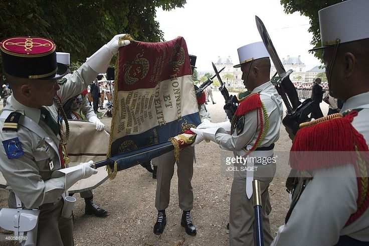 Soldiers of the French Legion Etrangere (Foreign Legion) from the 3rd REI based in Kourou, French Guiana, fold their flag after a ceremony in the Luxembourg Gardens in Paris, on July 13, 2015, the day before France marks Bastille Day celebrations. he motto of the regiment reads 'Honor and Loyalty'.