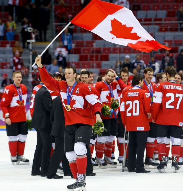 Team Canada forward and assistant captain Jonathan Toews waves the Canadian flag after Canada beat Sweden 3-0 in the men's gold medal ice hockey game at the 2014 Winter Olympics, Sunday, Feb. 23, 2014, in Sochi, Russia.