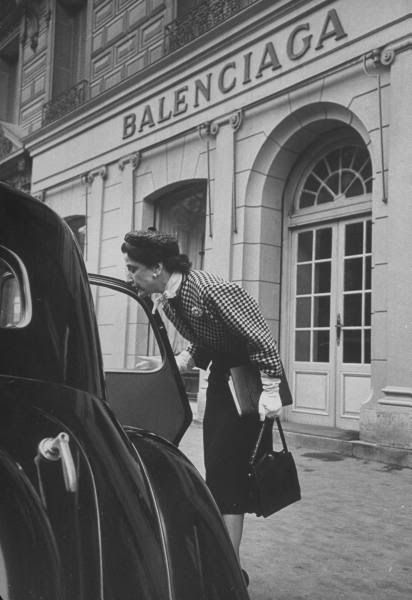 Bettina Ballard was the fashion editor of Vogue Magazine Through the 1940s and 1950s.  Bettina Ballard arriving at Balenciaga at 9:15am to select clothes while wearing a Balenciaga suit.  In the car are the coats and hats of the other fashion houses she will visit that day.