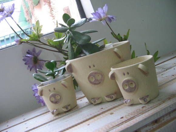 Jogo com três potes em formato de simpáticos porquinhos em cerâmica. Podem ser usados como vasinhos pra plantas ou porta trecos (escovas de dentes, maquiagens, material de escritório...) ótimos e fofíssimos organizadores! R$ 95,00