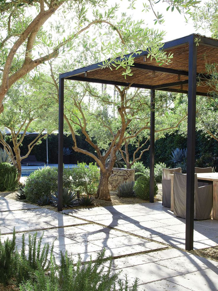 In this Hancock Park garden, a steel trellis provides shade and a living space that can be heated and lit with LED lights.