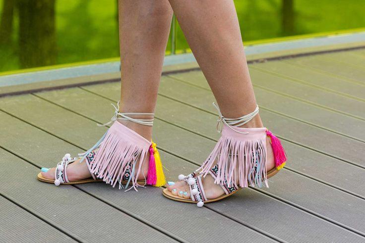 Sandalele de damă Mineli Tessieîn nuanțe dulci de roz pal și ornamentate cu barete brodate cu imprimeu aztec, ciucuri colorați și jucăuși și franjuri din piele, sunt ideale pentru a completa o ținută diafană într-o zi toridă de vară.