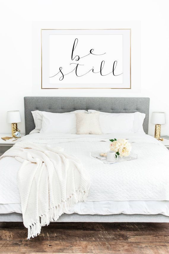"""Be still"" wall art...grey quilted headboard with gold bedside table lamps"