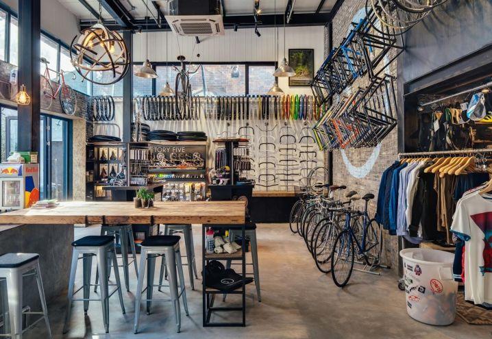Si respira un'atmosfera vivace al pianterreno di Factory 5, bike store e caffetteria inaugurata lo scorso anno a Shanghai. Line House ha organizzato la zona ristoro con gli sgabelli Tolix Stools e un tavolone con top in legno di seconda mano