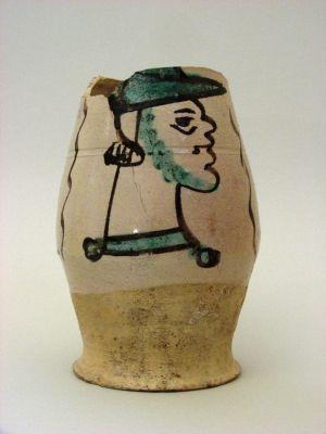 Boccale biconico in maiolica arcaica. II° metà del XIV secolo. Decorazione centrale con profilo di uomo barbuto con cappello, in verde ramina e bruno manganese