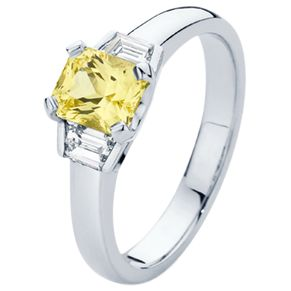 A lovely yellow sapphire nestled between two trapezoid diamonds.