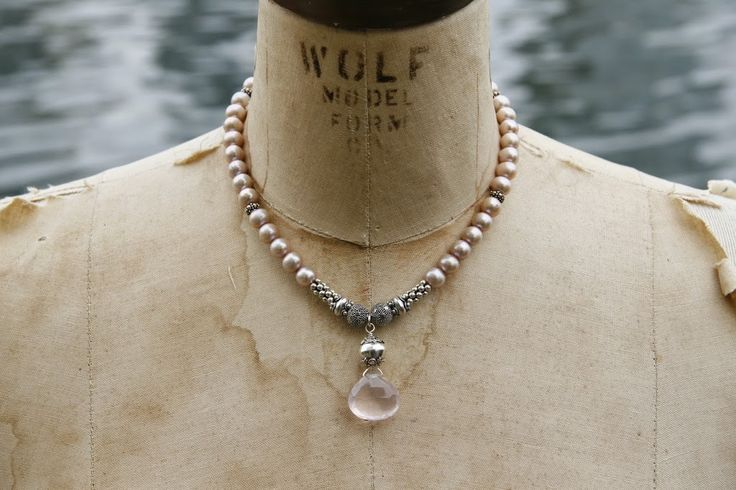 A collar of pale pink pearls mixed with sterling silver beads and accented with a large rose quartz pendant.