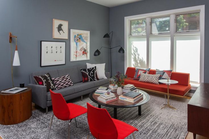 The midcentury modern sofas are the anchor pieces in this living room.  By adding vintage side and coffee tables, a Serge Mouille-style floor lamp, a gray-and-white ombre rug, and pops of bright red along with the newly painted gray walls, the space becomes an eclectic, sophisticated room suitable for entertaining and relaxing.