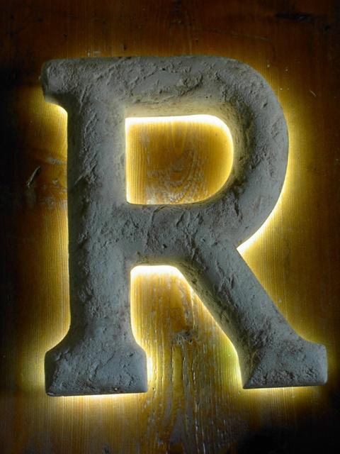Lettera in pietra scolpite a mano con inserimento neon catodo freddo per illuminazione luce indiretta.  www.guidoborgonovo.it