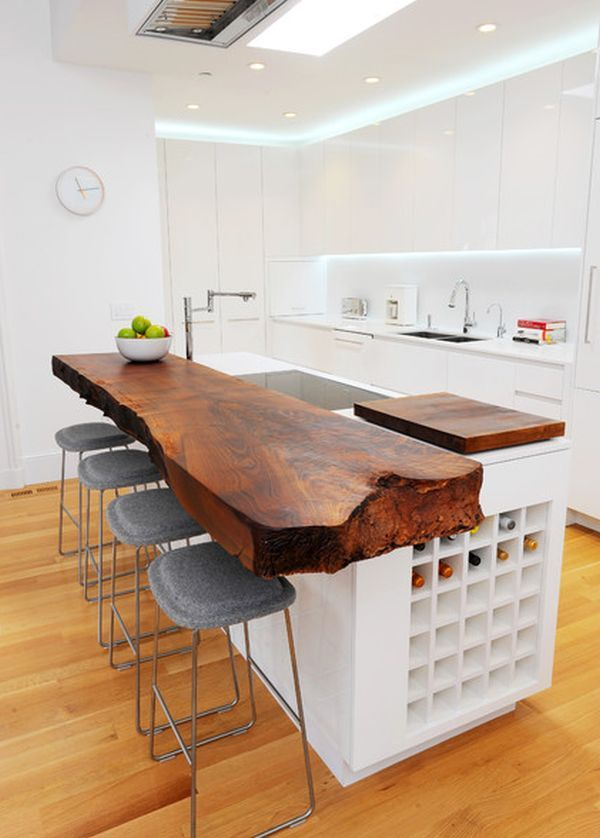 This kitchen has an overall modern and simple design. The only element that definitely stands out is the wooden countertop. It has a very nice stain and patina but the natural edge is definitely the most interesting detail. It stands out even more in this white décor.