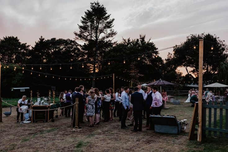 The DIY outside area complete with ice cream cart, festoon lighting, case full of blankets and tables and chairs. Photo by Benjamin Stuart Photography #weddingphotography #weddingreception #receptiondecor #outsidespace #eveningparty #chillout