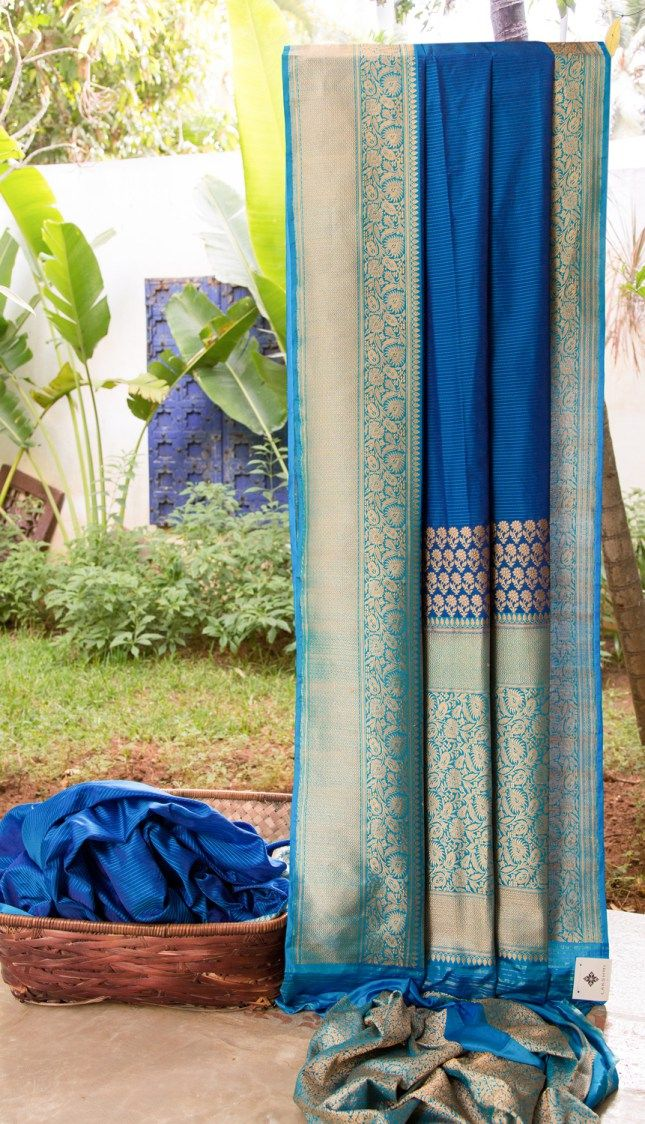 This lapis blue Benares silk is striped with cerulean blue. The border and pallu have intricate gold zari weave over a cerulean blue base adding richness to this piece