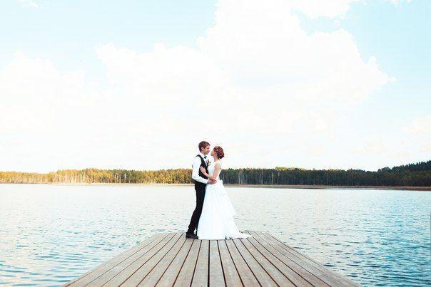 Жених и невеста на понтоне. Вокруг озеро, небо и далекий другой берег