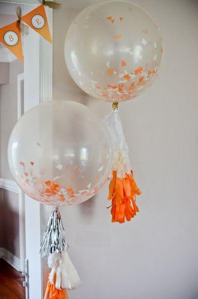 Decora con globos transparentes de látex rellenos de confeti los arcos de la entrada a tu fiesta.