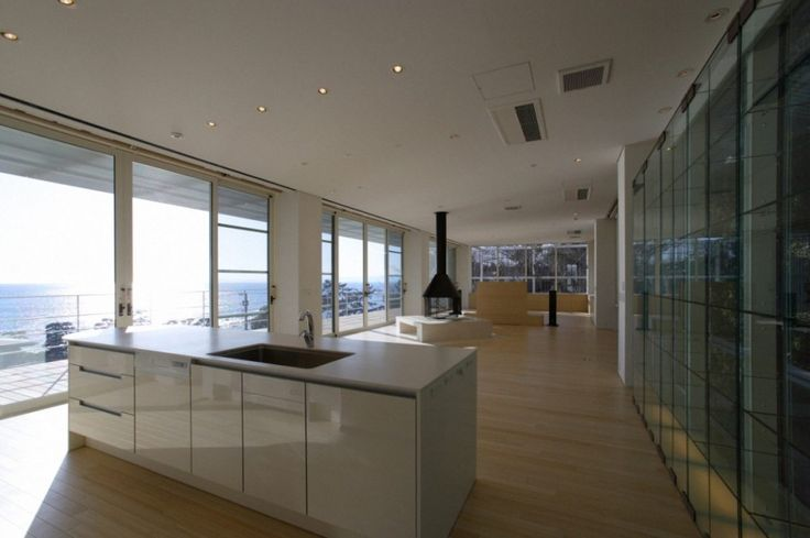 Architecture, Sweet Kitchen With White Wooden Countertop Kitchen Sink With Stainless Faucet Transparent Clear Glass Wall And Glass Shelves Wall Wooden Floor And White Ceiling With Downlight Fireplace With Black Hood: Modern Villa Design Encompassing the Brightness and Airy Atmosphere