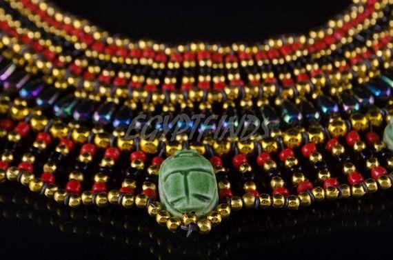 Esta mano hizo Cleopatra collar características hermosas color decorados por escarabajos brillantes 7 granos Atraerá elogios con cualquier equipo. Detalles: Tamaño (aprox.): Un tamaño cabe todos Dimensiones (aprox.): Circunferencia: 33,5(85,5 cm) Alrededor cuello: rango de 17 a 19