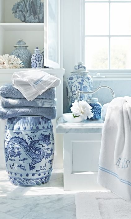 Blue and white porcelain accent pieces in bathroom with garden stool, and monogrammed linens