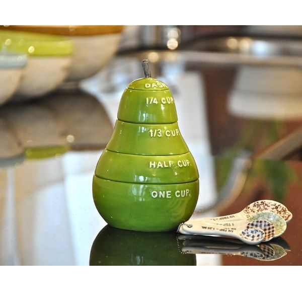 "As Featured in Shape Magazine! Add a splash of color in your kitchen with this charming set of measuring cups cleverly stacked in the shape and color of a pear.   Decorative and functional, this set of 5 measures - one cup, half cup, 1/3 cup, /4 cup, and topped with a dash.  Rae Dunn design.  Glazed ceramic.  Green color.  6.5""Wx6""H"