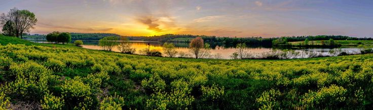 A sunset shimmers over the lake and fields of March Creek State Park, Pennsylvania.