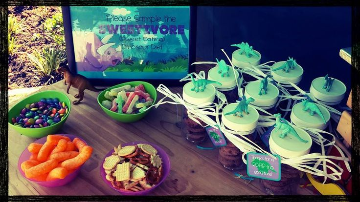 Sweet  and cake table: DIY plastic dino containers with choc chip cookies as party favours. Picture frame with the definition of a sweetavores and sweets and snacks.