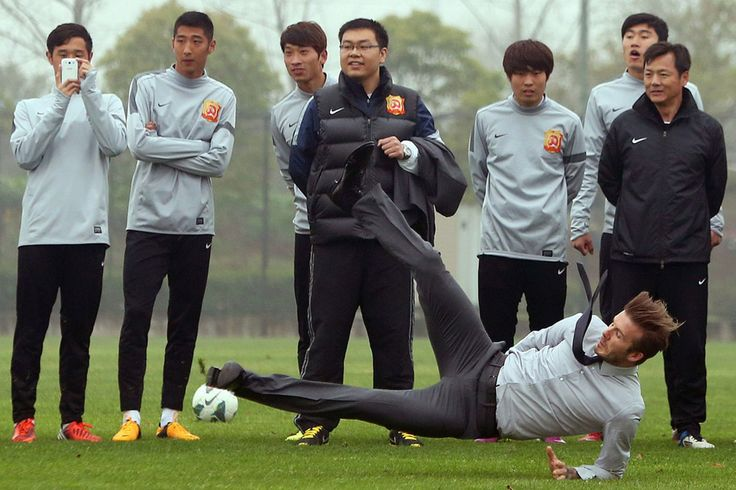 Football superstar David Beckham (R) falls down after illustrating how to take a free kick during a visit to the Zall Football Club in Wuhan, central China's Wuhan province on March 23, 2013. Beckham raised the prospect of one last stop on his global football journey on March 20, refusing to rule out playing in China after his contract with Paris Saint-Germain ends. CHINA OUT AFP PHOTO