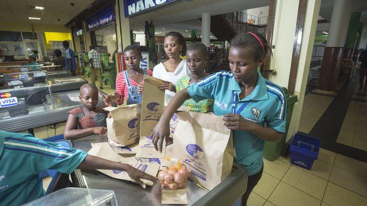 Rwanda - Sonia (13 jaar, 2e van rechts) en Shania (12 jaar, 2e van links) uit Rwanda krijgen in de supermarkt altijd een papieren zak om hun boodschappen in te doen.. Plastic tassen zijn verboden.