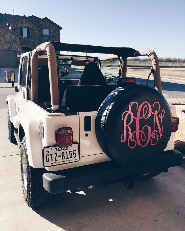 topless white jeep with monogram tire cover