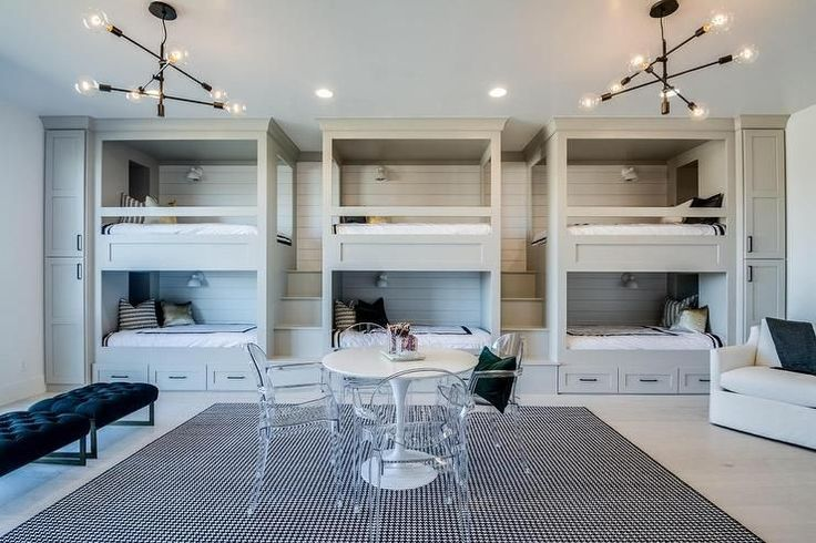 Contemporary boys' bunk room features gray shaker cabinets flanking three sets of side by side gray built-in bunk beds set atop of storage drawers accented with brass pulls positioned in front of a white pedestal table surrounded by four ghost chairs sat on a black and white rug illuminated by two contemporary brass pendants.