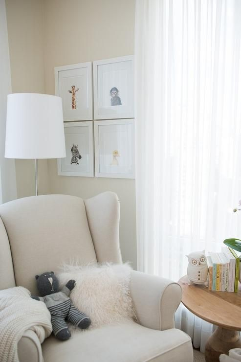 Beautiful nursery corner features a collection of framed Sharon Montrose The Animal Print Shop Prints over a PB Kids Wingback Nailhead Rocker draped in a cream throw and white sheepskin pillow situated next to a round salvaged wood accent table illuminated by a polished nickel floor lamp.