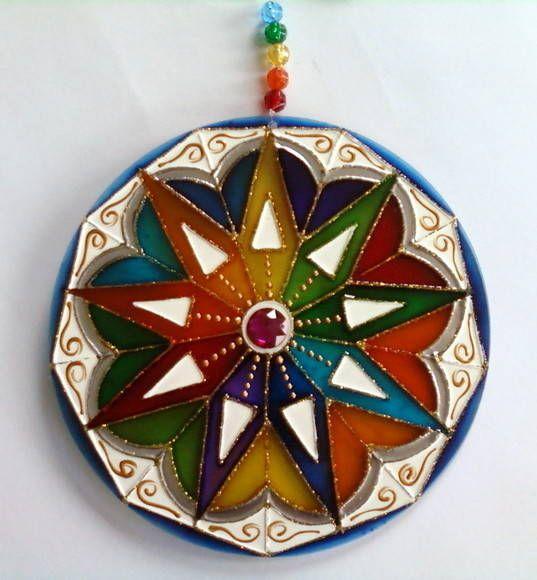 Mandala em acrílico de 15cm de diâmetro, pintura vitral, decorada com tinta relevo dourada e pedrinhas acrílicas em ambos os lados. R$ 27,00