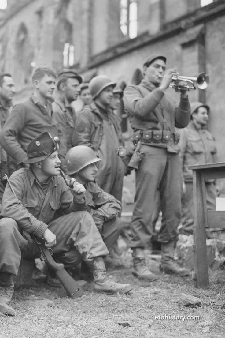 March 10, 1945: Soldiers from the 274th Infantry Regiment at Behren-lès-Forbach, France, listen to their regimental dance band during their first break from combat for several months. The performance took place alongside Église Saint-Blaise, a neo-Gothic church built in 1910. Three soldiers in the photo wear traditional German Trachten hats adorned with pins.