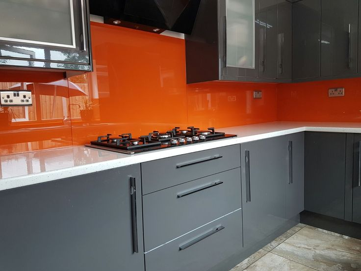 bespoke glass splashbacks fitted to a home kitchen painted in stunning orange to contrast white worktops & matt grey cupboards