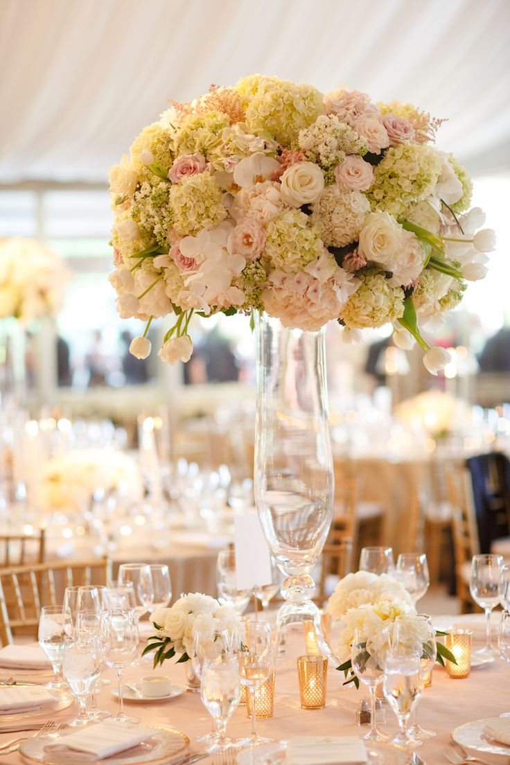 A tall, romantic centerpiece brimmed with ivory & blush florals. Photography: Karlisch Studio. Read More: http://www.insideweddings.com/weddings/southern-chic-wedding-in-oklahoma-with-performance-by-boyz-ii-men/697/