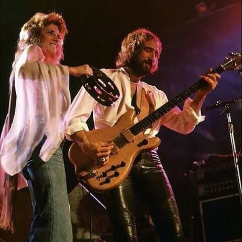 Stevie  ~ ☆♥❤♥☆ ~   wearing street clothes onstage with John McVie who's wearing leather pants and a smile and looking super cool, 1975