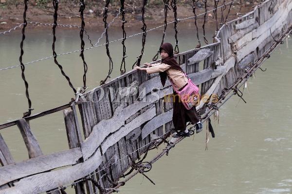Bertaruh Maut Menuju Sekolah  Siswa SD Negeri 02 Sangiangtanjung meniti jembatan rusak menyeberangi Sungai Ciberang, Kampung Ciwaru, Desa Sangiangtanjung, Kec. Kalanganyar, Kab. Lebak, Banten, untuk menuju sekolah, Sabtu (21/1/2012). Jembatan sepanjang 94 meter ini rusak akibat banjir bandang di sungai tersebut. Mereka nekad menyeberang jembatan rusak tersebut untuk mempersingkat perjalanan menuju sekolah.