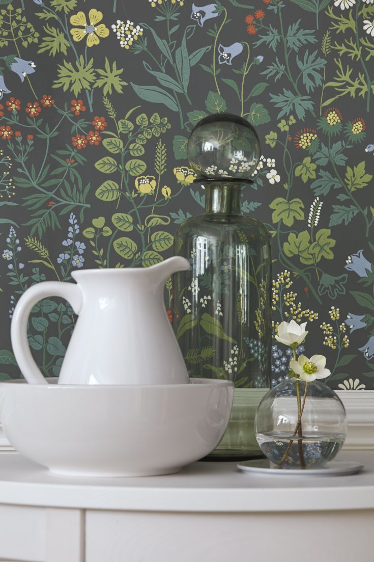 A pretty floral wallpaper design featuring a plethora of wild flowers including daisies and buttercups set against a charcoal background.