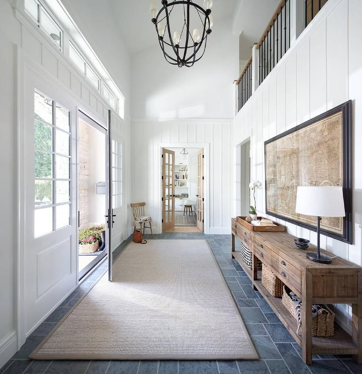 Chic foyer features a two story ceiling accented with a Lancaster Chandelier illuminating a wall clad in board and batten lined with a double pine printmaker's console table and a vintage map art piece.