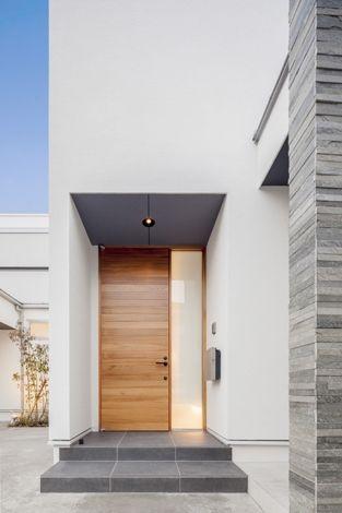 真っ白な外壁に映える玄関ドア(『道後のコートハウス』共に成長し、共に時を刻む住まい)- 外観事例