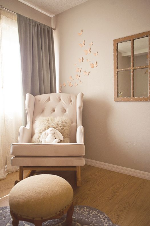 """The """"big splurge,"""" according to Kelli, was her Nurseryworks Empire rocker. The burlap ottoman is from a local vintage store, and the cutout peach butterflies on the wall are from Bug's Loft."""